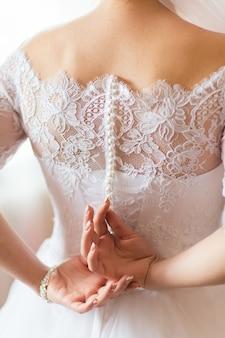 De bruid maakt de knopen van de jurk vast met haar handen