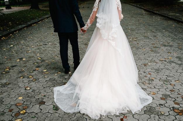 De bruid met bruidsboeket en bruidegom gaat weer op de stoep en houdt elkaars hand vast tijdens een wandeling door de straat in de stad. pasgetrouwden van het buitenleven.