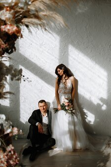 De bruid met een boeket en de bruidegom zittend op de vloer. op de achtergrond van de huwelijksboog