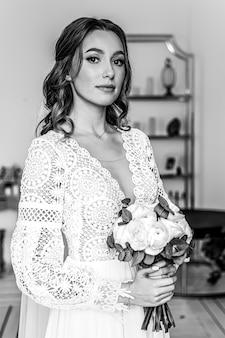 De bruid met een boeket verse bloemen in een mooie feestelijke jurk met kant.