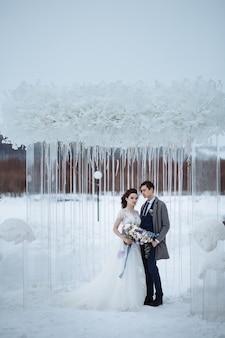 De bruid met een mooi boeket en de bruidegom op de bruiloft winter schieten. jongeren staan tegen de achtergrond van winter bruiloft decoraties