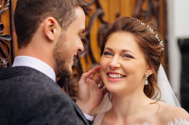 De bruid met prachtige sieraden glimlacht oprecht glimlachend in de buurt van haar man