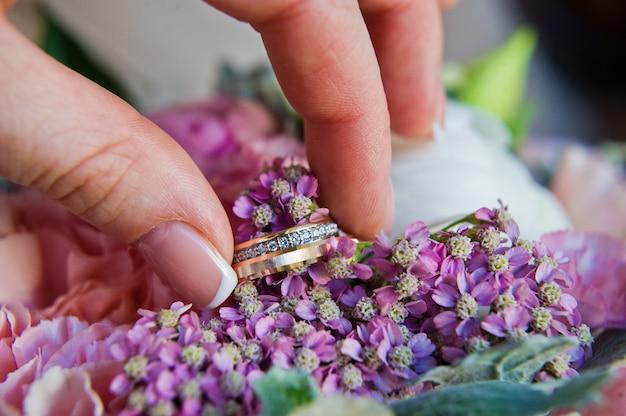 De bruid neemt de hand van gouden trouwringen met diamanten.