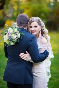 De bruid omhelsde haar bruidegom en kijkt vooruit