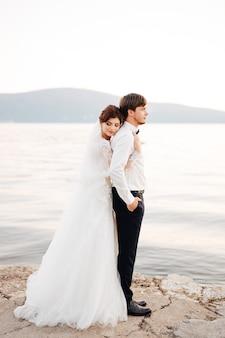 De bruid omhelst de bruidegom en laat haar hoofd op zijn rug rusten op de pier bij water