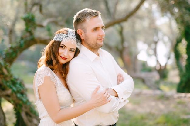 De bruid omhelst de bruidegom van achteren en legt haar hoofd op zijn schouder midden in een prachtig park