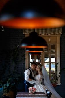 De bruid omhelst zacht de bruidegom binnen. emotionele jonggehuwden knuffelen bij het raam. glimlachend bruidspaar in een kamer met een stijlvol interieur met lampen. trouwdag