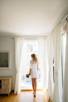 De bruid op blote voeten in een witte peignoir staat bij het raam met een bruidsboeket in haar handen