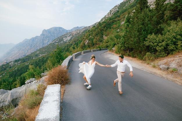 De bruid rolt op een skateboard en houdt de hand vast van de bruidegom die langs de snelweg rent