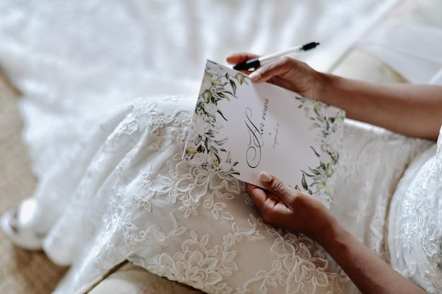 De bruid schrijft de huwelijksgeloften, de symbolen van de huwelijksdag
