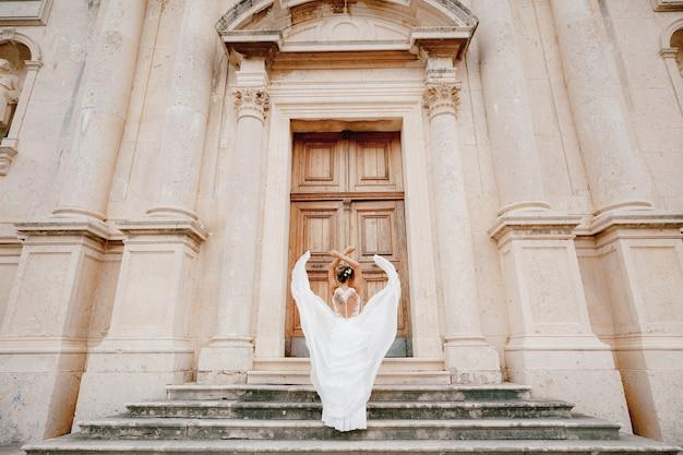De bruid sloeg haar armen over haar hoofd en haar rok fladdert om haar heen op de oude trappen van de kerk