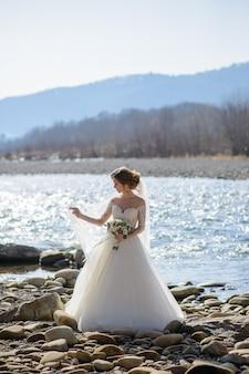 De bruid speelt met een sluier op een bergrivier. houdend een huwelijksboeket in zijn handen.