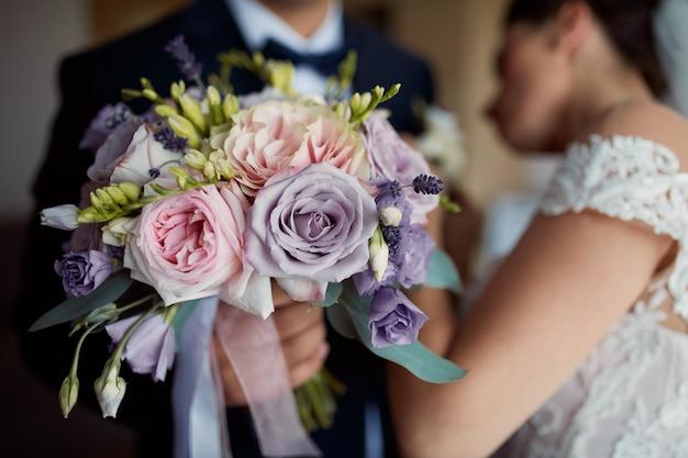De bruid speldt boutonniere aan het jasje van de bruidegom terwijl hij huwelijksboeket houdt