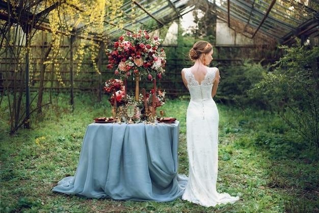 De bruid staat bij de bruiloftstafel.