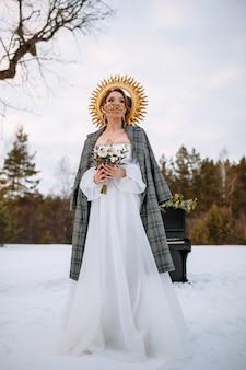 De bruid staat in een besneeuwd bos. de bruid draagt een fantastisch beschermend masker