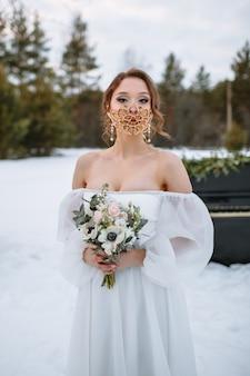 De bruid staat in een besneeuwd bos. de bruid met een fantastisch beschermend masker.