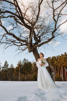 De bruid staat in een besneeuwd bos naast een droge boom