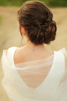 De bruid staat met haar rug naar de sluier