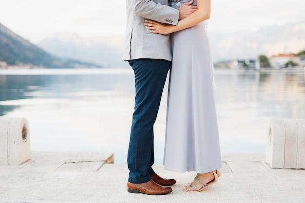De bruid stond op haar tenen voor de bruidegom en omhelsde haar tegen de achtergrond van de kust