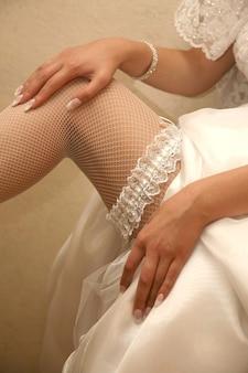 De bruid toont haar bruiloftskousenband