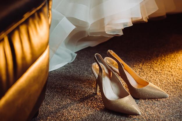 De bruid toont witte trouwschoenen