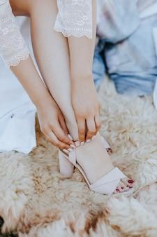 De bruid trekt mooie huwelijkssandalen aan. meisje in sandalen met hakken op een trouwdag