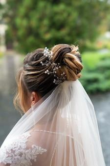 De bruid van het huwelijkskapsel met juwelenclose-up