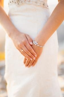De bruid vouwde haar handen met een trouwring aan haar vinger en een armbandclose-up