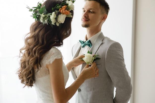 De bruid zet een corsages op het jasje van de bruidegom.
