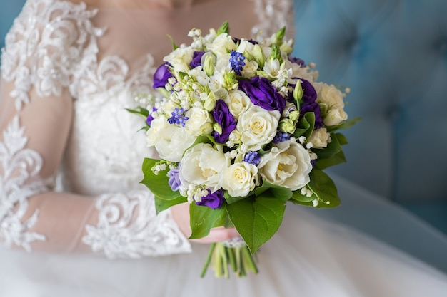 De bruid zit en houdt een close-up van het huwelijksboeket