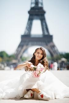 De bruid zit in snickers vóór de toren van eiffel in parijs