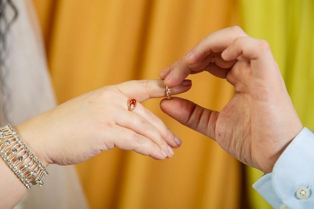 De bruidegom die de bruid op de wijsvinger zet op de joodse bruiloft hand close-up. horizontale foto