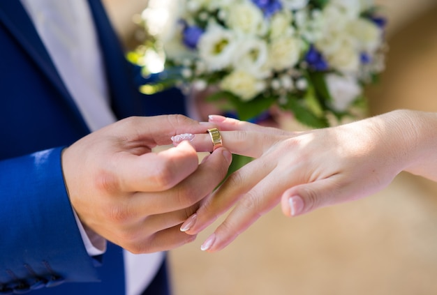 De bruidegom doet een gouden trouwring aan de vinger van de bruid