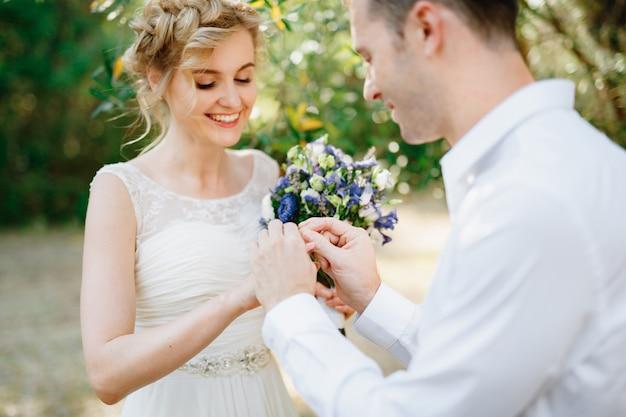 De bruidegom doet een ring aan de vinger van de bruid tijdens de huwelijksceremonie, de bruid houdt een boeket vast en glimlacht