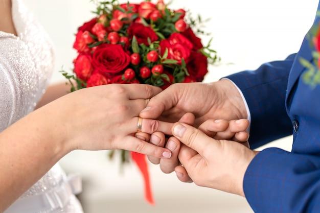 De bruidegom doet een trouwring aan de vinger van de bruid. bruiloft details.