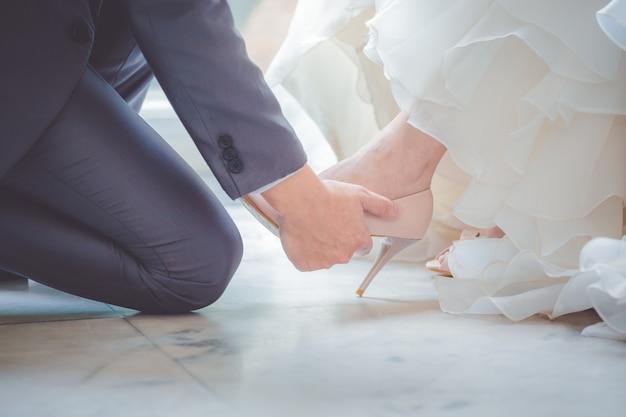 De bruidegom draagt schoenen voor de bruid