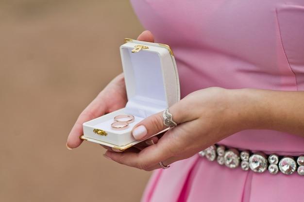 De bruidegom en de bruid houden een gouden trouwring in haar hand