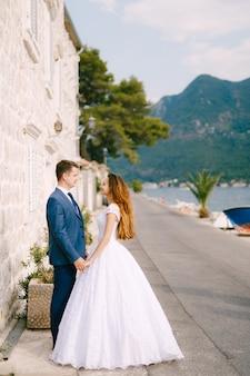 De bruidegom en de bruid houden elkaars hand vast en kijken elkaar aan