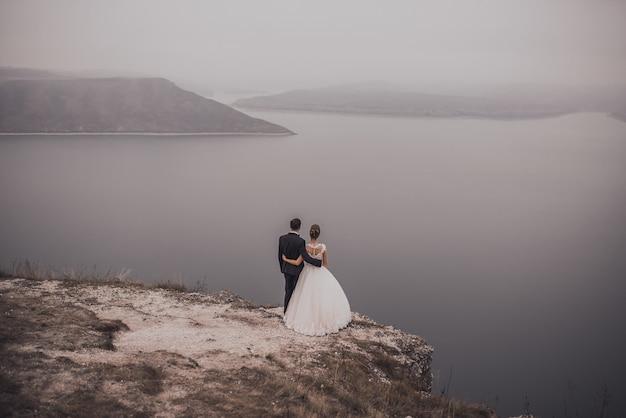 De bruidegom en de bruid in een klassieke trouwjurk staan op een klif