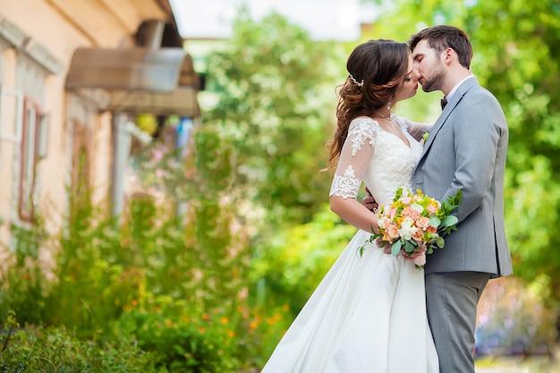 De bruidegom en de bruid met boeket staan in het park