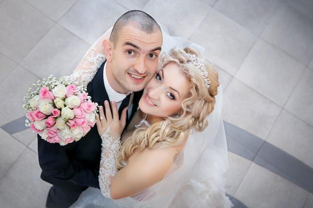 De bruidegom en de bruid met een huwelijksboeket van rozen in een hand kijken omhoog
