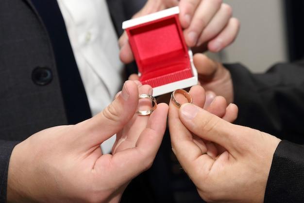 De bruidegom en zijn getuige die een close-up van de trouwring dragen