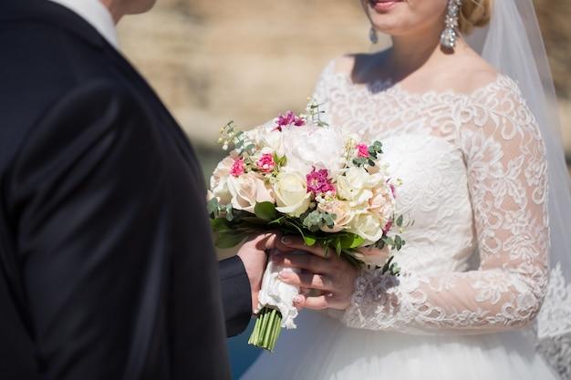 De bruidegom geeft het boeket van de bruid
