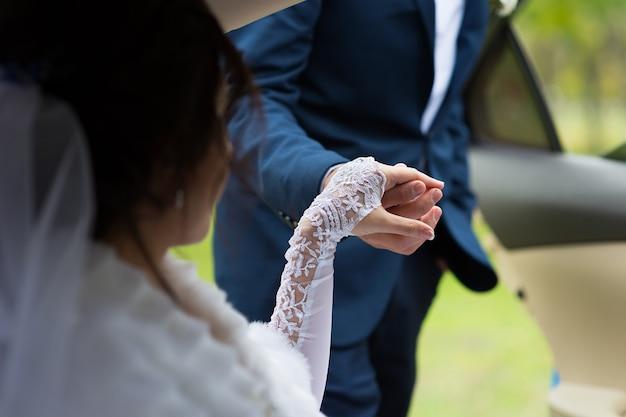 De bruidegom geeft zijn hand aan de bruid in de auto