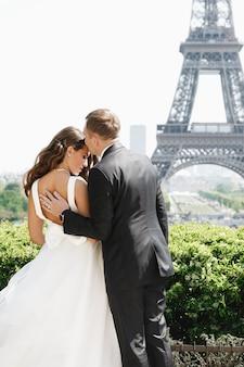 De bruidegom houdt bruid achter teder status vóór de toren van eiffel in parijs