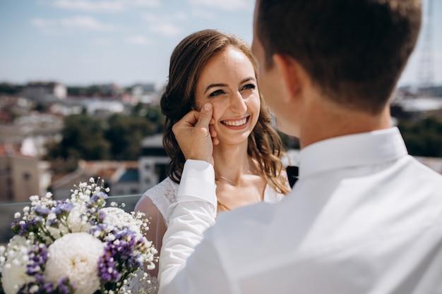De bruidegom houdt bruid teder status op het dak met grote de zomercityscape rond hen