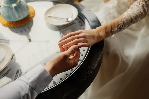 De bruidegom houdt de bruid bij de hand. detailopname. liefdevolle bruid en bruidegom zitten in een café. thee drinken. liefde, bruiloft concept. gelukkig pasgetrouwde stel.
