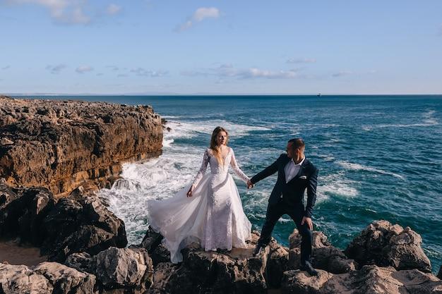 De bruidegom houdt de bruid bij de hand en ze lopen langs de rotsachtige kust van de oceaan