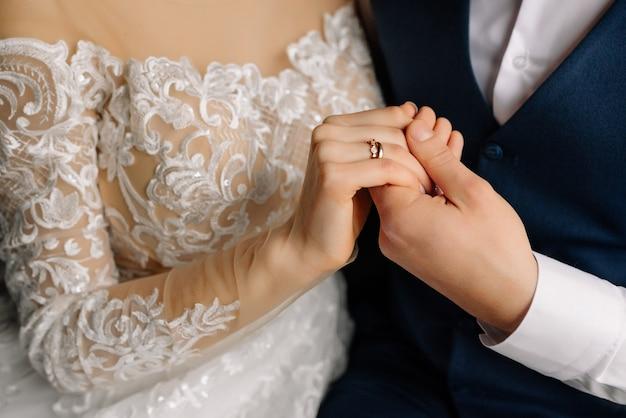 De bruidegom houdt de bruid bij de hand met ring. mooie elegante paar jonggehuwden verliefd. bruiloft concept. detailopname.