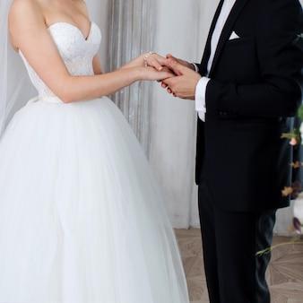 De bruidegom houdt de hand van de bruid, huwelijksgeloften.